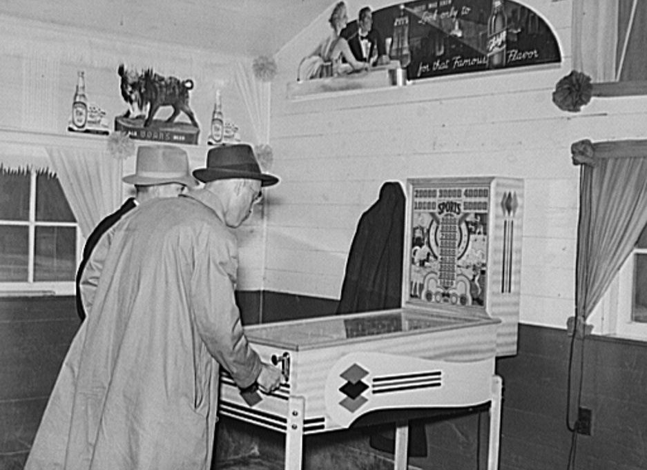 Tobacco buyers playing at pinball machine during lunch hour on day of                   tobacco auctions. Durham, North Carolina, 1939